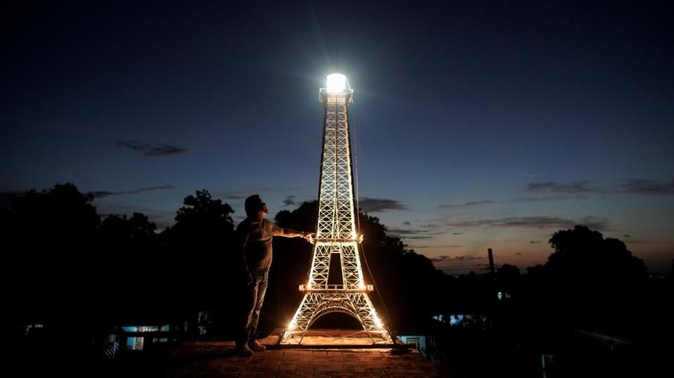 Jorge Enrique Salgado poses for a photo beside a replica of the Eiffel Tower he built on the roof of his home in Havana, Cuba, August 7, 2020. (REUTERS/Alexandre Meneghini)