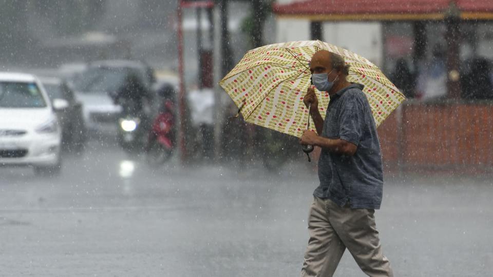 A man walks with umbrella as it rains at Dadar in Mumbai.