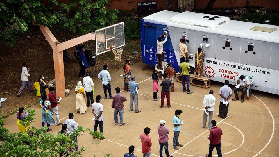 People stand in a queue to test for Covid-19 near a mobile swab collection vehicle, at Indira Gandhi Municipal Corporation Stadium, in Vijayawada.