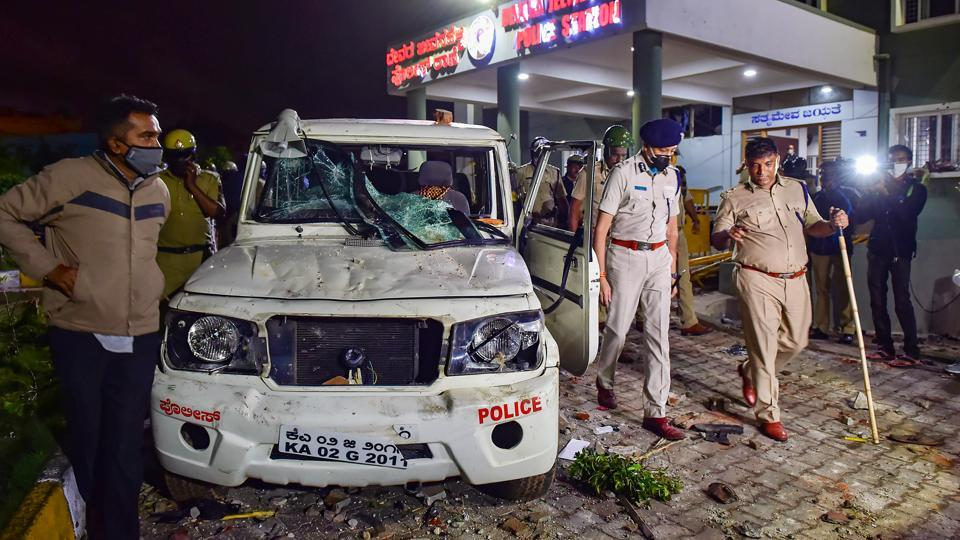 Police stand guard after a mob vandalised a police station following a social media post by a relative of a MLA, in Bengaluru.