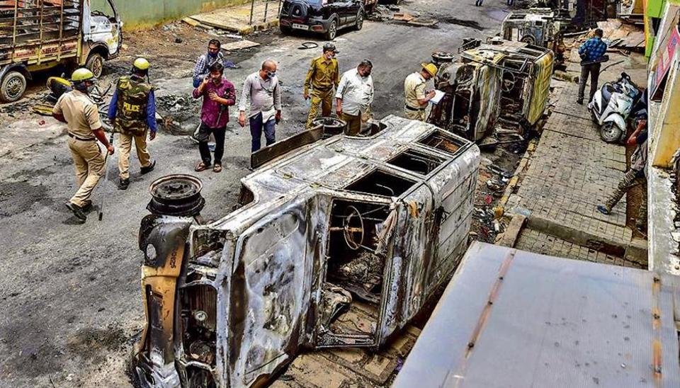 Police and residents walk past charred remains of vehicles vandalised by a mob over a social media post in Bengaluru on Wednesday.
