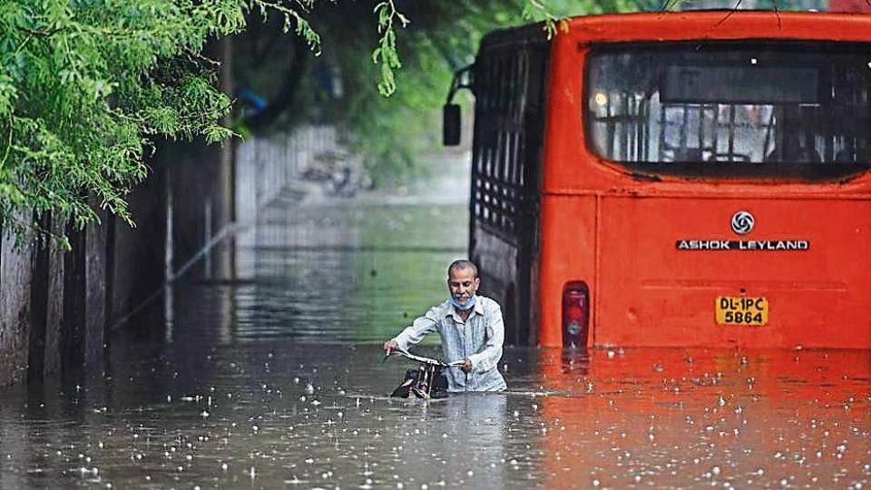 A cyclist makes his way while a bus is seen partially submerged at Zakhira underpass.