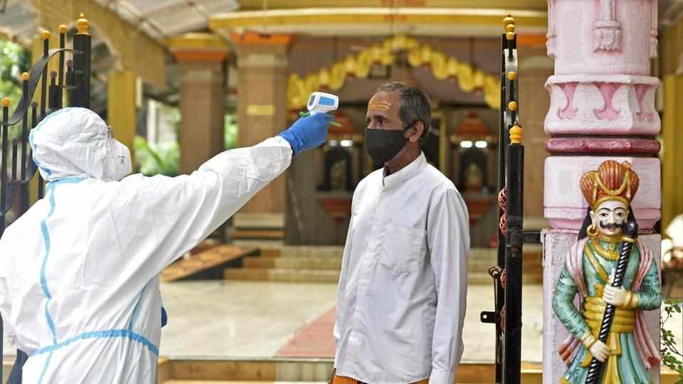 Health care staff check the temperature and pulse rate of Priest of a temple at Malad(E) during Covid-19 pandemic in Mumbai.