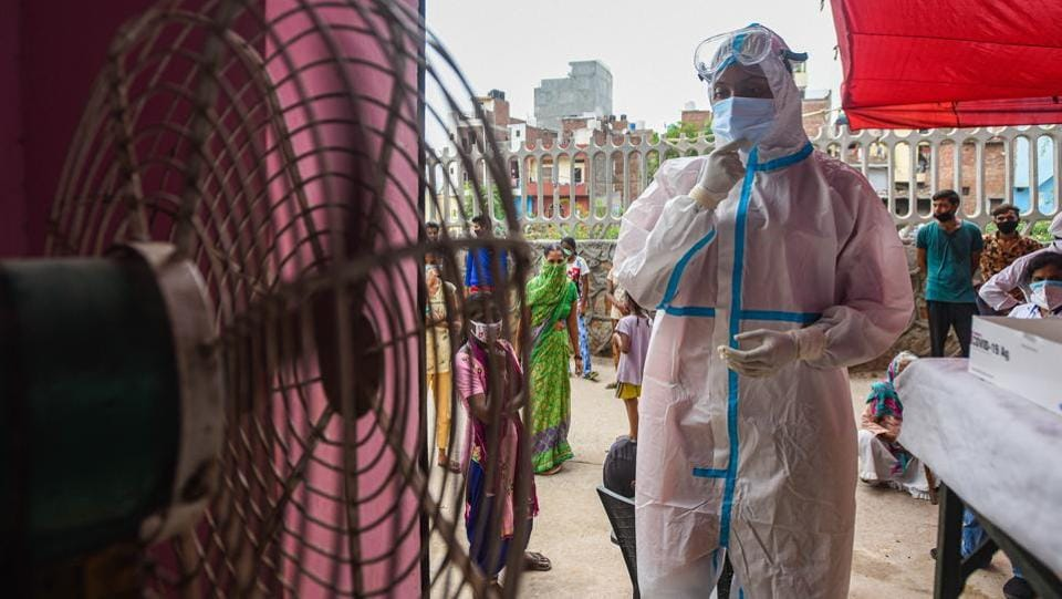 A health worker cools off in front of a pedestal fan while collecting swab samples to test for Covid-19 at Mehrauli in New Delhi on August 10. Between August 12 and 13 morning, India recorded its highest single-day coronavirus disease (Covid-19) recoveries so far, in excess of 56,000, taking the overall recovery rate to 70%, HT reported. (Amal KS / HT Photo)