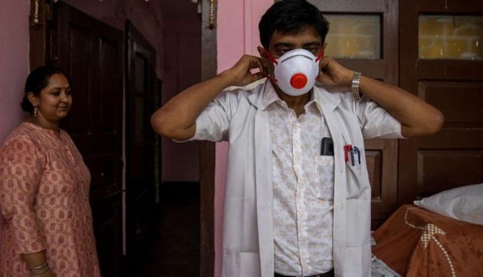 Dr. Kumar Gaurav, 42, a medical professor and consultant psychiatrist who has been named the top official at Jawahar Lal Nehru Medical College and Hospital during the coronavirus disease (Covid-19) outbreak, puts on his personal protective equipment (PPE) as his wife Dr. Mili Jaswal, a psychologist, looks on, at their home in Bhagalpur, Bihar, India.