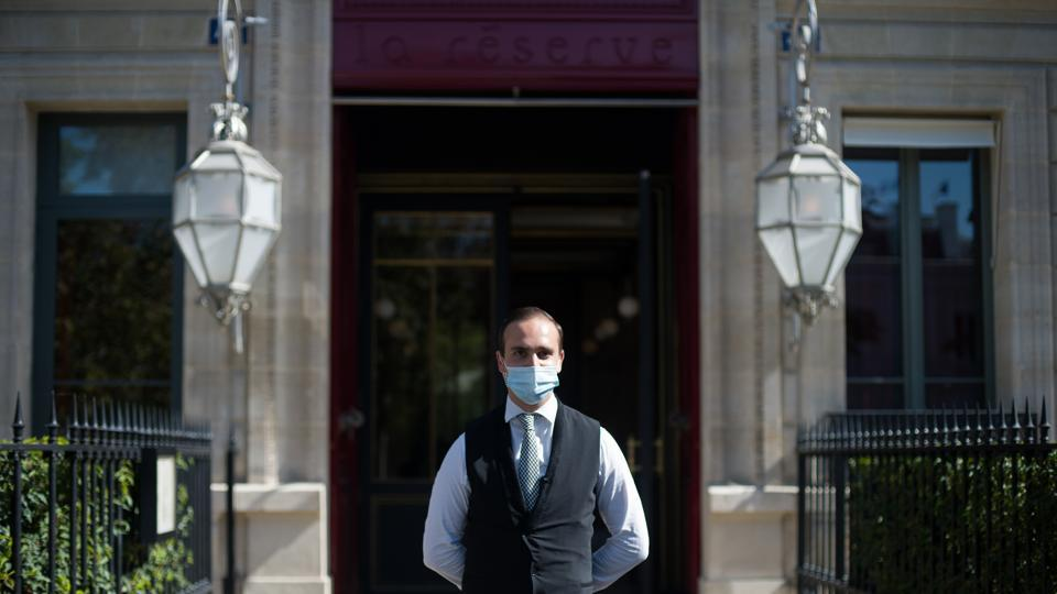 A doorman wearing a protective face mask stands outside the La Reserve hotel, one of the 12 high-end hotels in Paris that are classified as palaces, in this arranged photograph in Paris, France, on Wednesday, Aug. 12, 2020.
