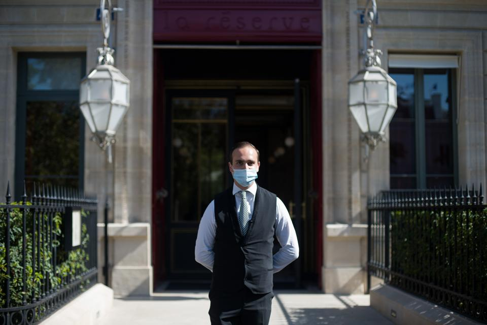 A doorman wearing a protective face mask stands outside the La Reserve hotel, one of the 12 high-end hotels in Paris that are classified as palaces, in this arranged photograph in Paris, France, on Wednesday, Aug. 12, 2020.  (Bloomberg)