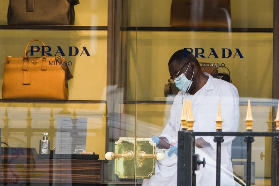 An employee sanitizes the front doors of the Prada SpA store on Avenue Montaigne, in Paris, France, on Wednesday, Aug. 12, 2020.  (Bloomberg)