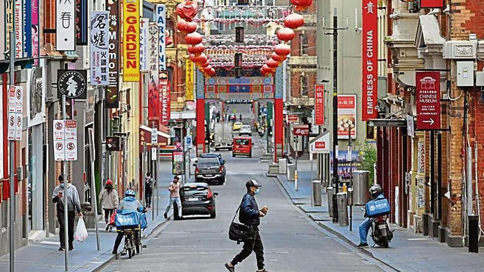 A man crosses a quiet road in Melbourne's Chinatown area on Thursday.