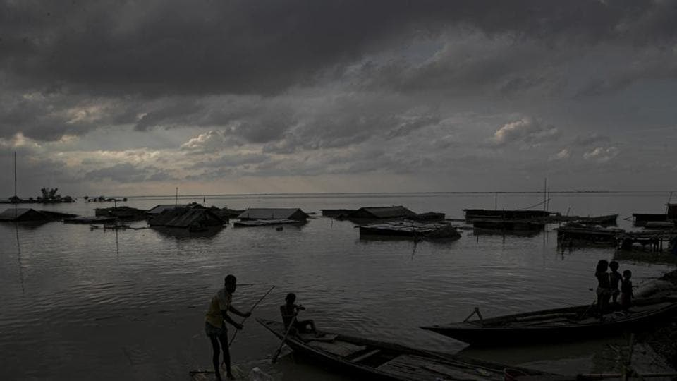 Flood affected people on boats are seen near their submerged houses in Morigaon district, Assam.