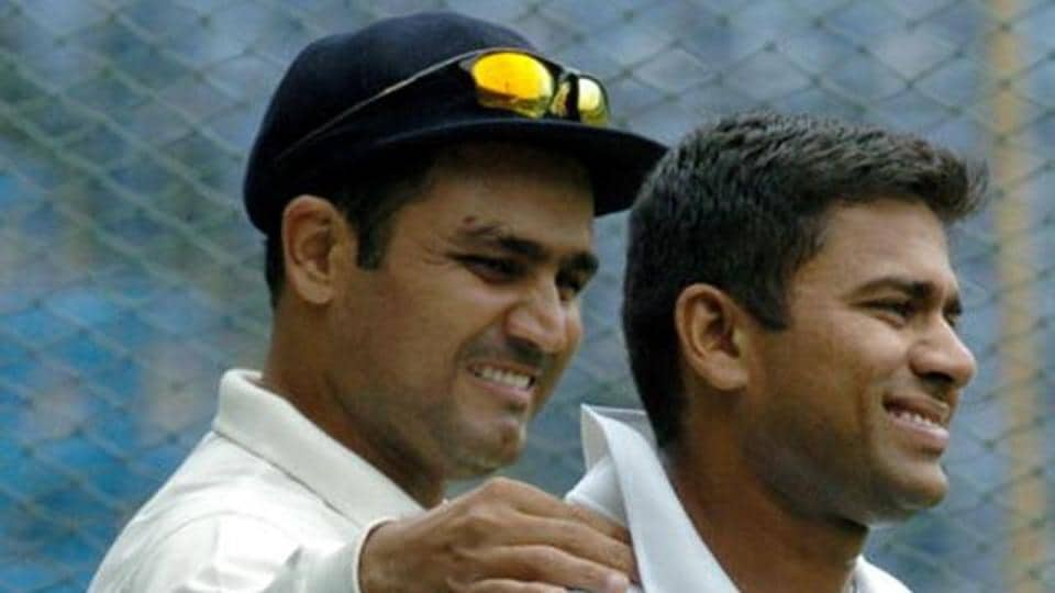 Indian cricketer Virender Sehwag (L) massages teammate Akash Chopra's shoulder during a practice session at The M. Chinnaswamy Stadium in Bangalore.