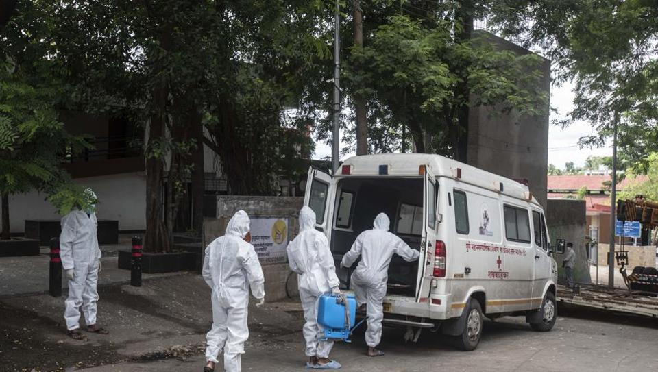 Contract workers in PPE equipment seen sanitizing the ambulance after transporting the body of a coronavirus victim, at Yerwada crematorium, in Pune.