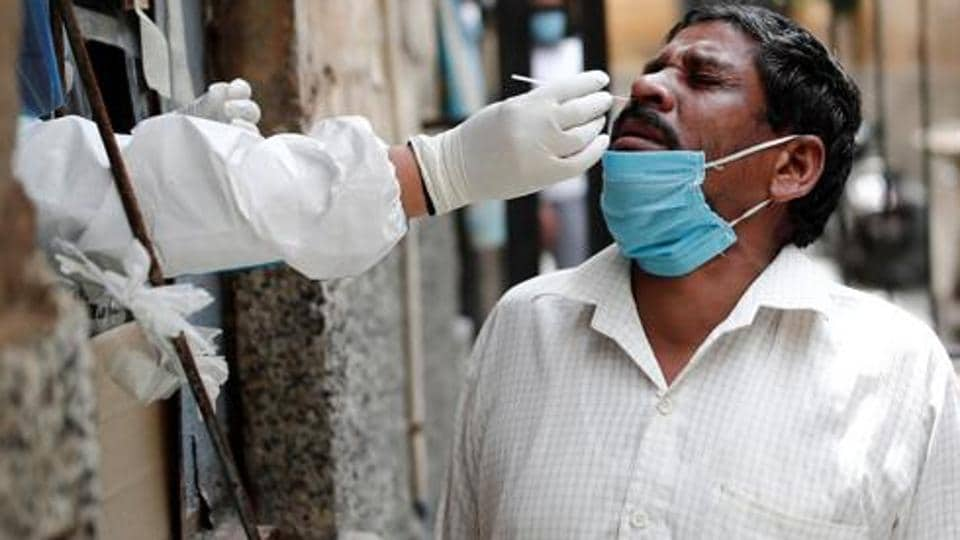 A health worker in personal protective equipment (PPE) collects a sample using a swab from a person at a local health centre in Delhi.