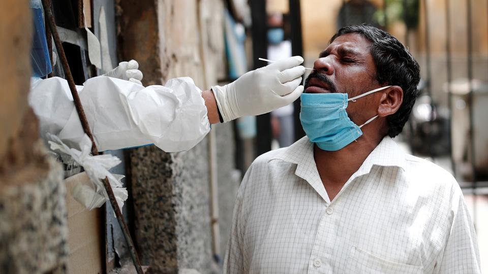A health worker in personal protective equipment collects a sample using a swab from a person at a local health centre to conduct tests for the coronavirus disease , Delhi, August 14, 2020