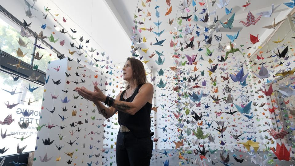 Artist Karla Funderburk, owner of Matter Studio Gallery, talks about the thousands of origami paper cranes hanging in an exhibit honouring the victims of Covid-19, in Los Angeles, Tuesday, Aug. 11, 2020. Funderburk started making the cranes three months earlier, stringing the paper swans in pink, blue, yellow and other colours together and hanging them in her gallery.  (AP Photo/Richard Vogel)