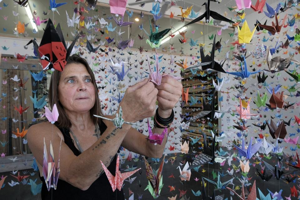 Artist Karla Funderburk, owner of Matter Studio Gallery, adjusts one of of the thousands of origami cranes hanging during an exhibit honoring the victims of COVID-19, Tuesday, Aug. 11, 2020, in Los Angeles. Funderburk started making the cranes three months earlier, stringing the paper swans in pink, blue, yellow and many other colors together and hanging them in her gallery. (AP Photo/Richard Vogel) (AP)