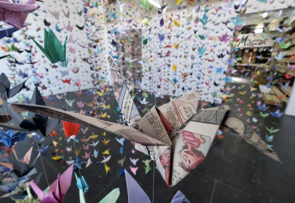 An origami crane made from a newspaper comic strip hangs with thousands of others during a memorial exhibit for the victims of COVID-19 at the Matter Studio Gallery, in Los Angeles, on Tuesday, Aug. 11, 2020. Hundreds of origami now hang from the ceiling of Karla Funderburk's Matter Studio with others sitting on tables and stacked in boxes waiting to be added to the sad reminder of the virus' toll. (AP Photo/Richard Vogel) (AP)