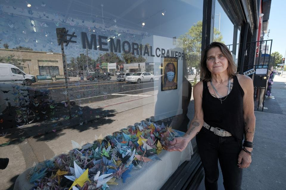 Artist Karla Funderburk, owner of Matter Studio Gallery, poses outside her gallery displaying a window of origami paper cranes during an exhibit