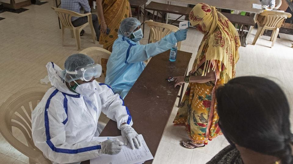 Healthcare workers check residents for Covid-19 during a free camp organised by Jagruti Mahila and Balkallyan Sanstha at Shivsagar City, Sun City road in Pune, India, on Thursday.