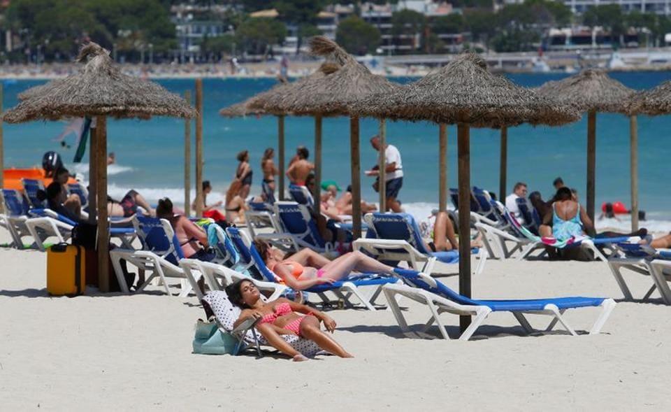 FILE PHOTO: People sunbathe in Magaluf beach, amid the coronavirus disease (COVID-19) outbreak in Palma de Mallorca, Spain July 11, 2020.