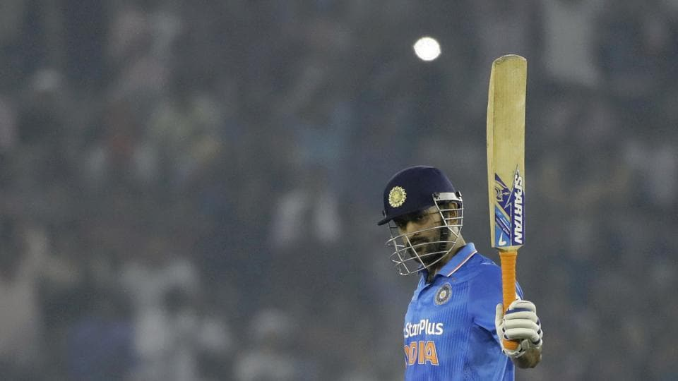 Indian cricket captain Mahendra Singh Dhoni raises his bat after scoring half a century during the third one-day international cricket match against New Zealand in Mohali.
