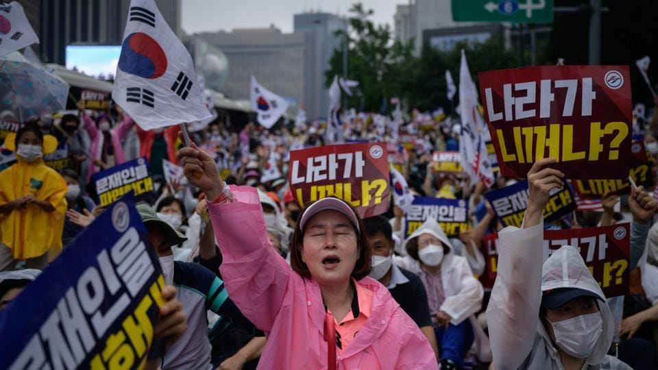 Anti-government protesters wave flags and raise slogans in Seoul on August 15. After a court allowed some protesters to go on, many of them paraded through rain near Seoul's presidential palace, calling for President Moon Jae-in to step down over what they see as kowtowing to North Korea, policy failures, corruption and election fraud, AP reported. (Ed Jones / AFP)
