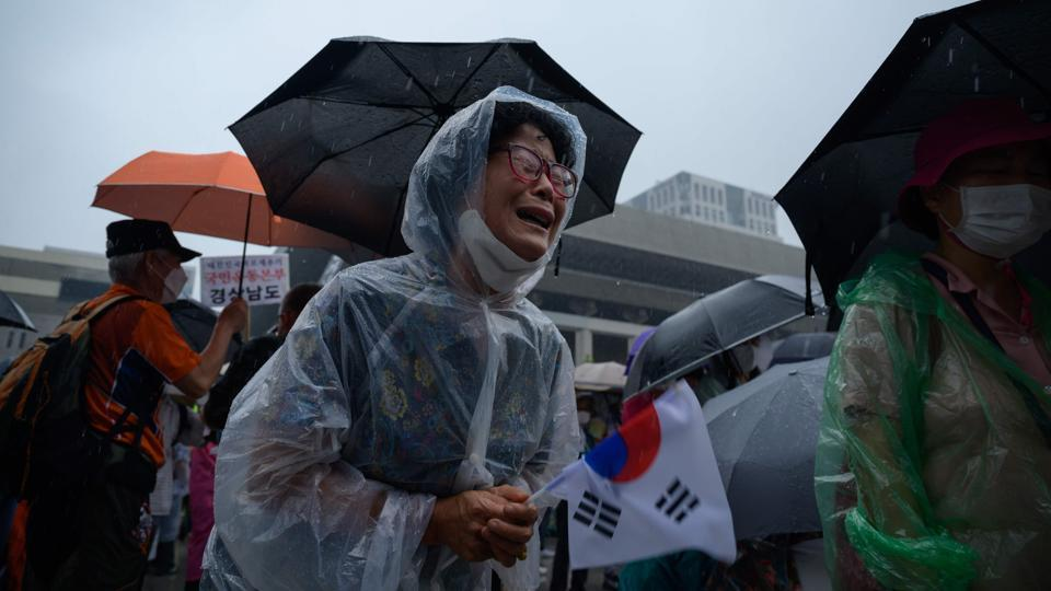 A woman weeps during the anti-government protest in Seoul on August 15. The two-week measures starting August 16 will allow authorities in Seoul and towns in neighbouring Gyeonggi Province to shut down high-risk facilities such as nightclubs, karaoke rooms, movie theatres and buffet restaurants if they fail to enforce proper measures. (Ed Jones / AFP)