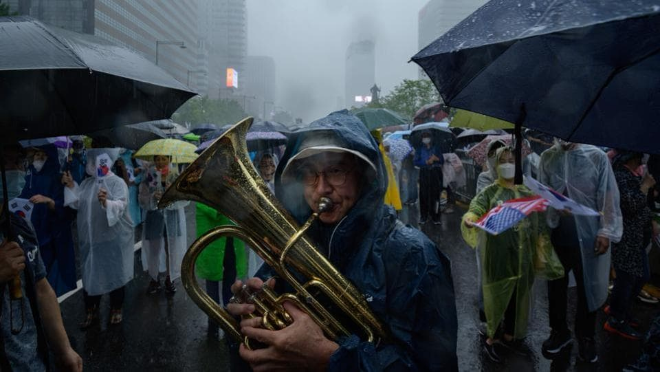 A protester plays a tuba during the anti-government protest in Seoul on August 15. The protests came as the government moved to impose stronger social distancing restrictions in the city and nearby towns following a spike in coronavirus infections. (Ed Jones / AFP)