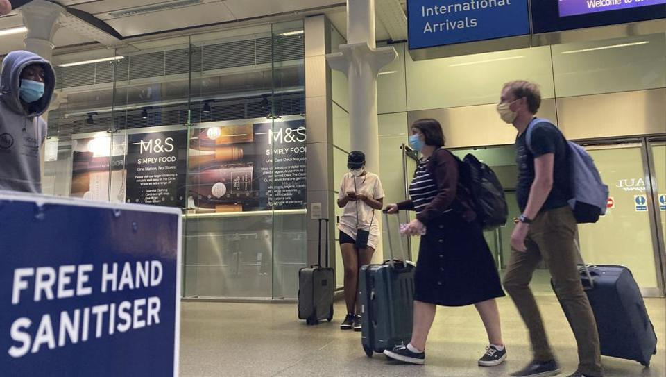Travellers emerge from the Eurostar St Pancras International railway station, returning from France Friday Aug. 14, 2020, to avoid the quarantine restrictions. Travellers have to return to the UK before the 4.00 am Saturday deadline, to avoid new quarantine regulations imposed on people returning from France because of the coronavirus. \