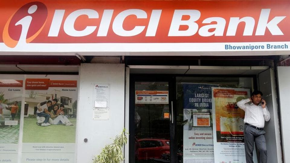 A man speaks on the phone outside an ICICI Bank branch in Kolkata, India.