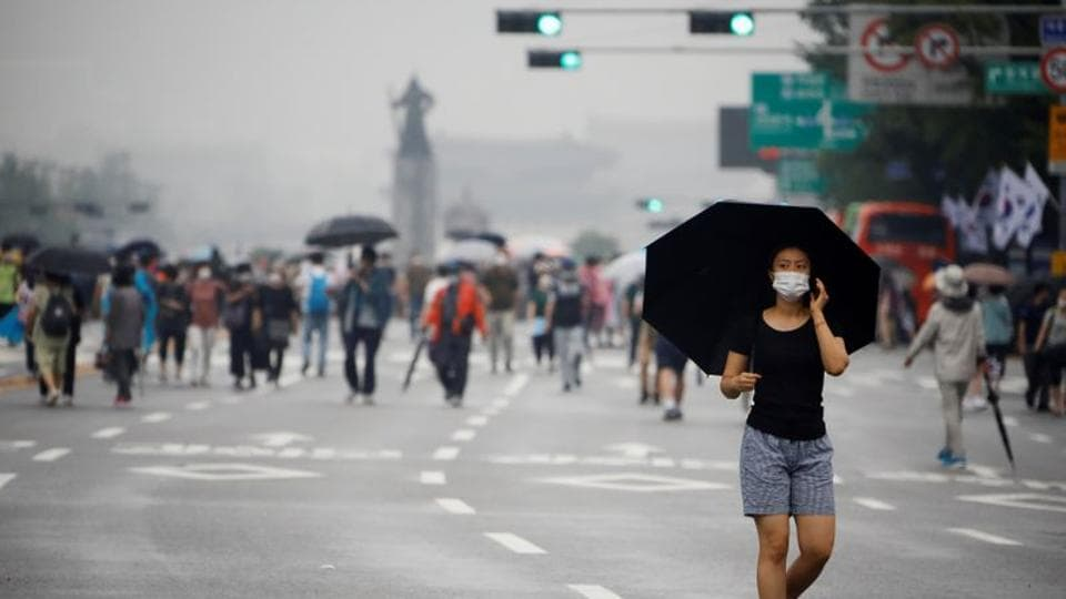 A woman wearing a mask walks past members of conservative civic groups taking path in an anti-government protest over fresh restrictions in Seoul on August 15. As in the Daegu case, authorities are facing some reluctance in cooperation and difficulty in tracking some members of the congregation. The outbreak led to a tightening of social distancing rules on August 16 despite protests. (Kim Hong-Ji / REUTERS)