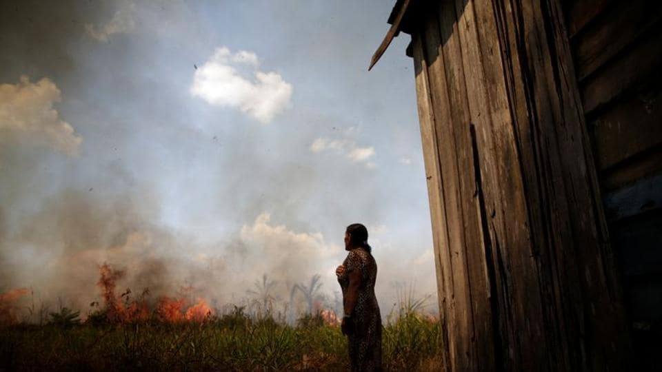 Miraceli de Oliveira reacts as the fire approaches their house in an area of the Amazon rainforest, near Porto Velho, Rondonia State, Brazil.