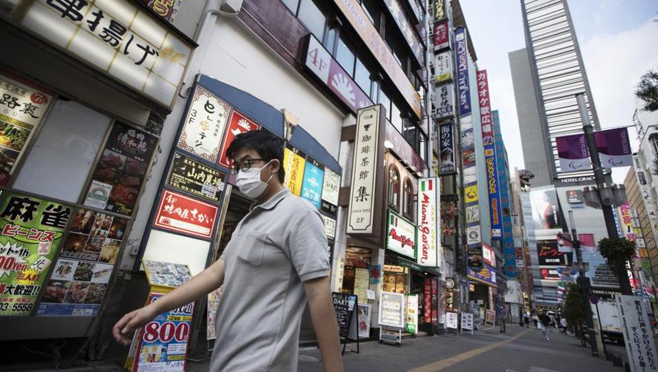 A man walks by restaurants in the Shinjuku district of Tokyo on Monday.