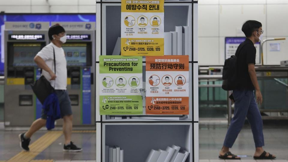 People wearing face masks pass by posters about precautions against the coronavirus at a subway station in Seoul on August 18. The Korea Centers for Disease Control and Prevention (KCDC) reported 246 new cases as of midnight on August 18, mostly in the Seoul metropolitan area, marking the fifth day of a three-digit tally. (Ahn Young-joon / AP)
