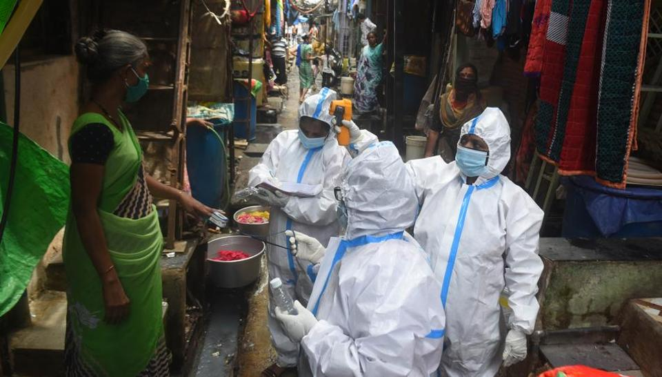 BMC Health worker and doctor conduct thermal screening and pulse test of a resident at Dharavi during Covid 19 pandemic in Mumbai