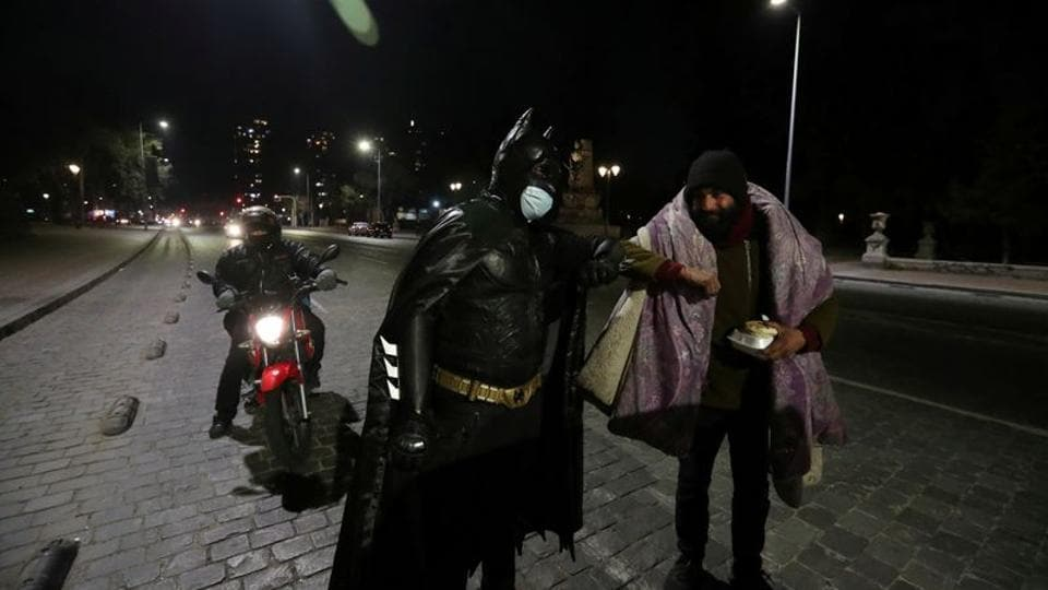 A Chilean trader and so-called 'Batman solidario' (Solidarity Batman) greets a homeless man with an elbow bump while delivering charity food rations in the street.
