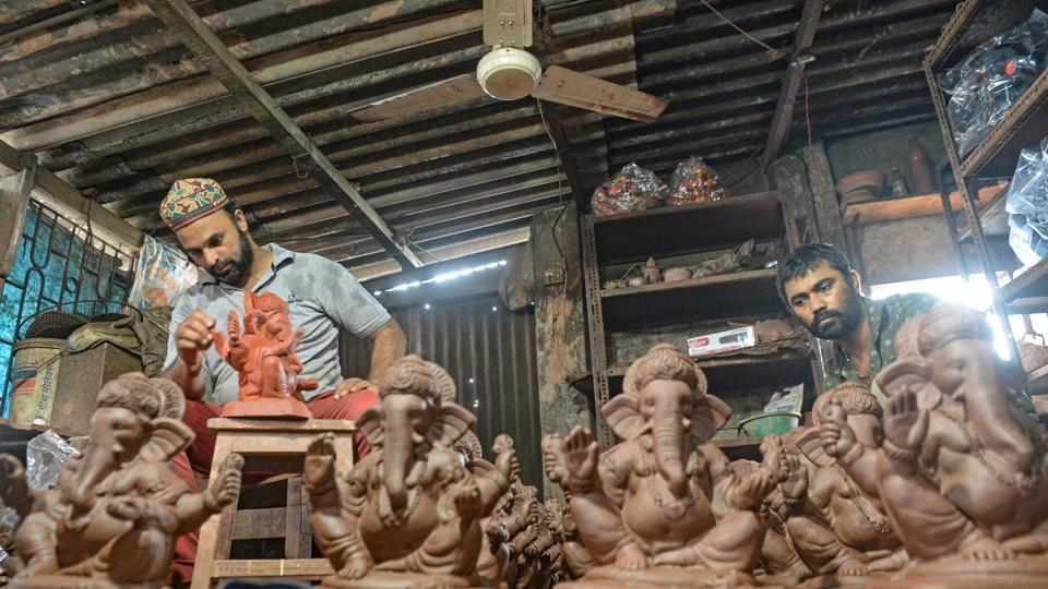 Potter Yusuf Zakaria Galwani (L) along with his colleague, works on the idols Hindu deity Ganesha at his workshop in Kumbharwada, Dharavi, Mumbai on August 15. After the coronavirus pandemic hit his pottery business, Galwani turned to a Hindu god to revive his fortunes by making environmentally-friendly Ganesha idols for the upcoming Ganesh Chaturthi festival.  (Indranil Mukherjee / AFP)