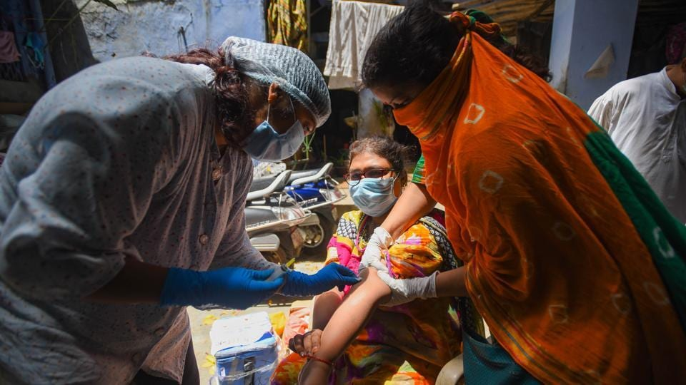 A medical worker collects a blood sample for the second serological survey sampling in early August in New Delhi.