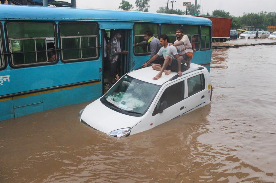 People taking refuge on a submerged car, Gurugram, August 19, 2020