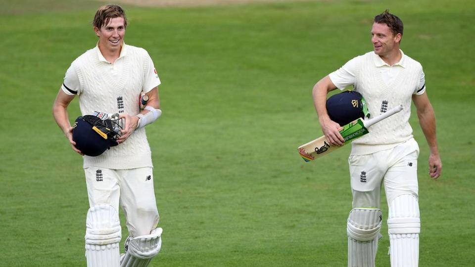 Zak Crawley (L) and Jos Buttler walk off the field at stumps on Day 1