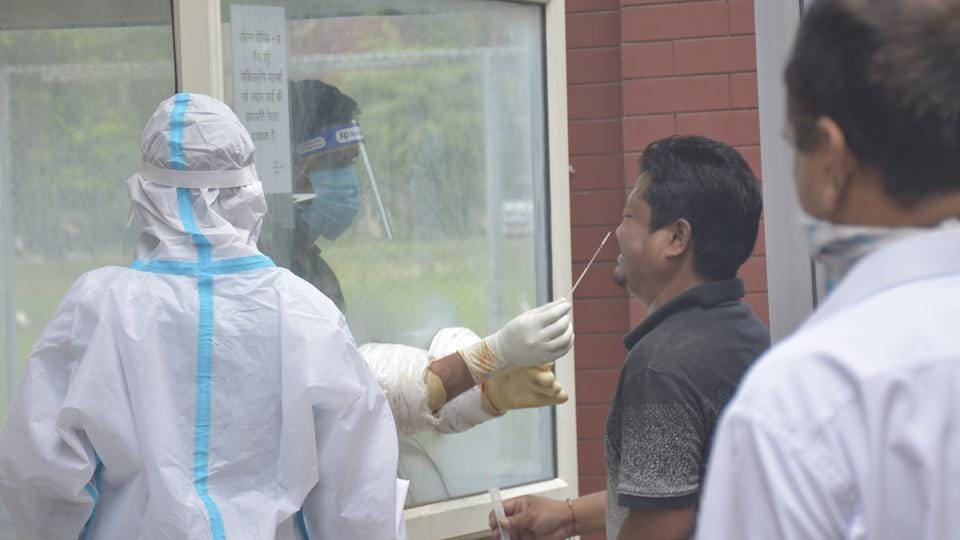 A health worker in PPE coveralls takes a swab sample from a man for coronavirus testing at IMS College in Ghaziabad.