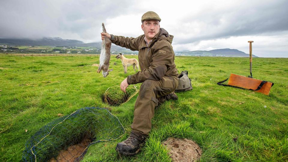 Professional rabbit catcher Steven McGonigal poses for a photograph with a caught rabbit as he hunts for them at County Donegal in northwest Ireland on August 18.  McGonigal is said to be Ireland's last traditional rabbit catcher, preferring ferrets, dogs, spades and nets instead of modern guns and poison. (Paul Faith / AFP)