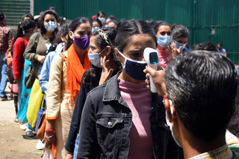 College staff checking the body temperature of students appearing foe exams in Shimla on Saturday.