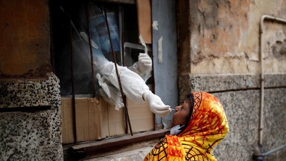 A health worker in personal protective equipment (PPE) collects a sample using a swab from a person at a local health centre to conduct tests for the coronavirus disease (Covid-19), amid the spread of the disease, in the old quarters of Delhi.