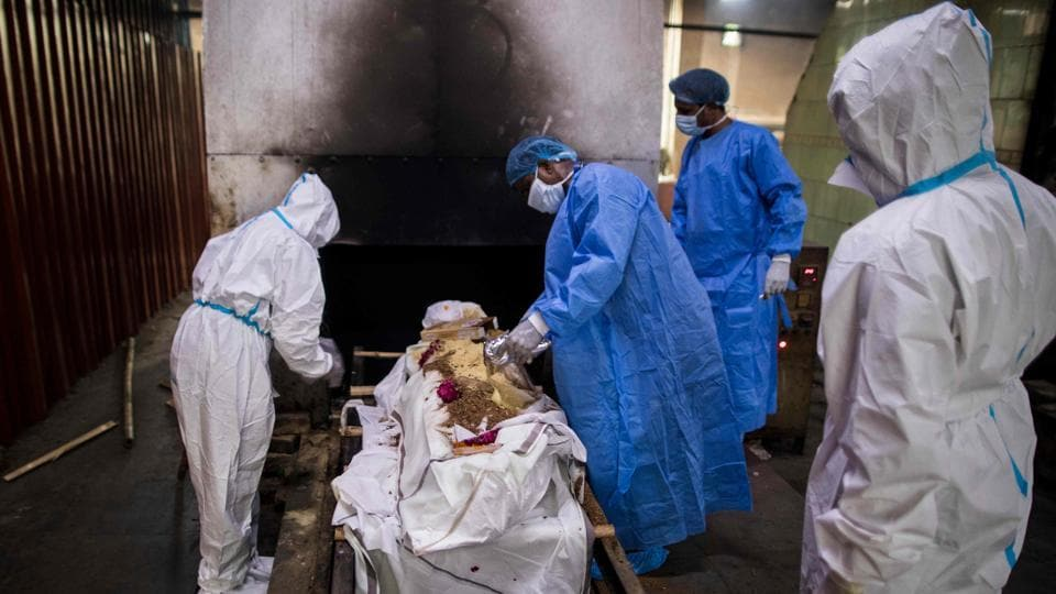 Relatives (in white) along with workers (in blue) wearing Personal Protective Equipment (PPE) prepare the body of a person who died from Covid-19 before cremation in New Delhi on August 22. The death toll from the pathogen stands at 56,706 after 912 fatalities were reported from across the country in the last 24 hours. According to the health ministry, the number of active cases stands at 707,668. (Xavier Galiana / AFP)