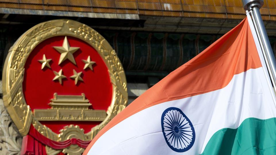 An Indian national flag is flown next to the Chinese national emblem outside the Great Hall of the People in Beijing.