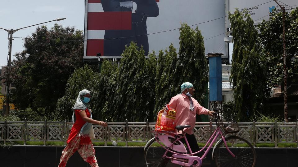 People wearing protective masks walk in front of a hoarding of Bollywood actor Amitabh Bachchan wishing him a speedy recovery, as he and members of his family were tested positive for coronavirus disease, in Mumbai.