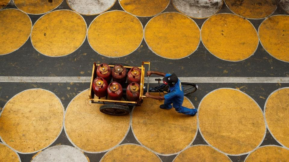 A man pushes a cart filled with liquefied petroleum gas (LPG) cylinders on a street painted with circles in Mumbai.
