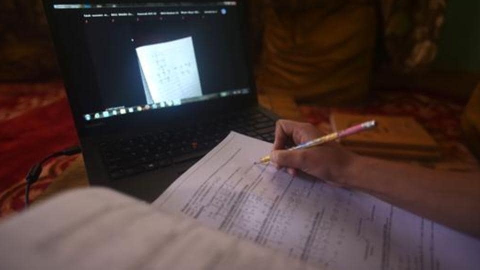 A student takes note while attending an online class at her home.