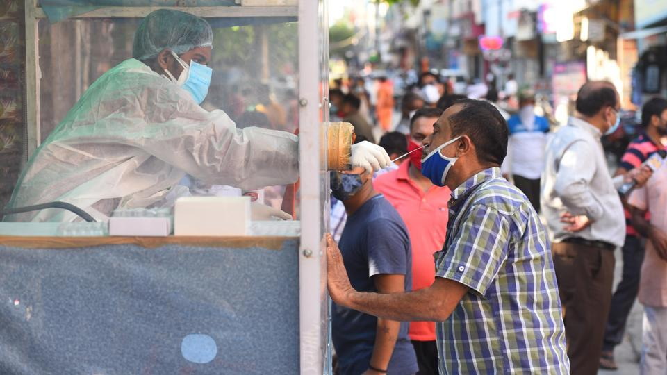 A health official collects a swab sample from a coronavirus testing kiosk set at a weekly market in Pandav Nagar, in New Delhi on Wednesday.